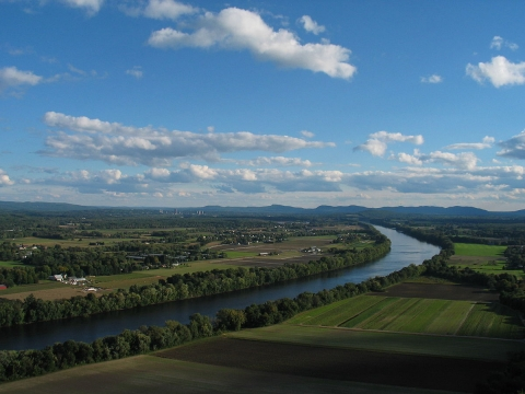 View looking south from Mt. Sugarloaf of Connecticut river winding its way towards bottom left of image, bordered on both sides by green farm fields. The distinctive peaks of the Holyoke range are in the background.