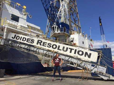 Photo of PhD candidate Adriane Lam standing in front of loading ramp to the ship Joides Resolution. Joides Resolution, in large capital letters adorns the loading ramp