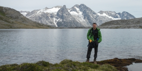 Picture of Greg DeWet standing in front of scenic lake with snow-capped peaks in the background