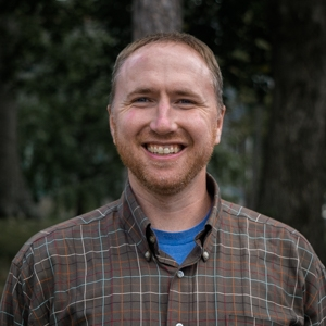 Portrait of Will Daniels, smiling, facing camera, in front of forested background