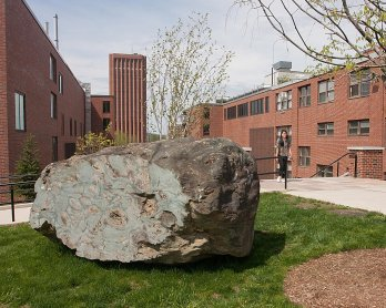Car-sized boulder of pillow lava sitting on lawn between two brick buildings built as fallout shelters in the 1950s.