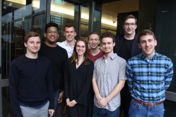 Photograph of Eight U-Mass undergraduates at 5 college geology symposium, standing in front of dimly lit hallway.