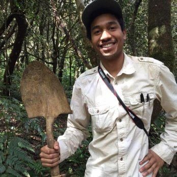 Portrait of Dr. Justin Richardson in field clothing in a forest, smiling at camera, holding shoveled with one hand, blade up.