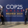 Dr. Benjamin Keisling, Dr. Julian Reyes, and Hannah Baranes, all in formal attire, striking poses in front of wall with dark blue COP25 logo.