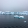long, low iceberg floating on dark grey sea with gloomy, dark, overcast sky in background