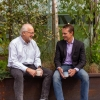 Dr.'s Curt Griffin (left) and Rob DeConto (right) seated on bench in front of young topiary, casually holding coffee mugs and smiling at one another.