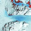 A satellite image shows the long flow lines as a glacier moves ice into Antarctica's Ross Ice Shelf, on the right. The red patches mark bedrock. USGS