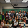 Over a dozen members of the U-Mass Geography club posing for a group photo within a classroom.