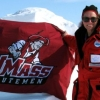 Photo of Dr. Julie Brigham Grette, smiling, wearing arctic cold-weather gear and sunglasses, holding U-Mass Minutemen flag in front of mountainous, snow-covered arctic landscape