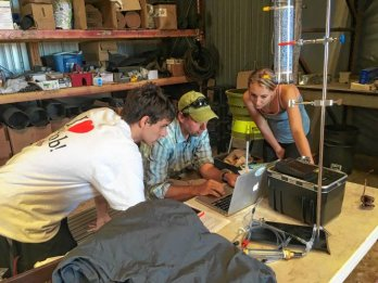 Three researches in field clothing, surrounded by equipment, one seated, gathered around a table in a science lab looking at a laptop.