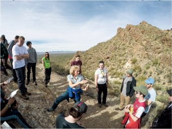 Dr. Sheila Seaman gesturing and teaching to group of students surrounding her on hillside of red-orange desert landscape with Saguaro cacti.