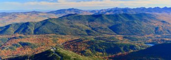 Fall scene of forest-clad Adirondack mountains upon mountains fading into distance.