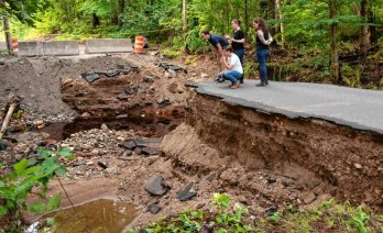 Rep. Jacob R. Olivera, kneeling, Sen. Eric P. Lesser, Conservation Commission Administrator Erica Larner, and Jen Turner, the chair of the select board in Belchertown, look over the damage on July 21 caused by the flooding on East Street in Belchertown on July 18. STAFF PHOTO/CAROL LOLLIS Testing Source: Daily Hampshire Gazette