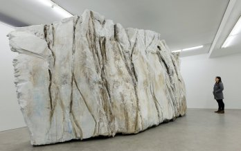 large sculpture resembling calved ice block, in white room with gray-clad, long-haired person for scale. Image source: MassMOCA