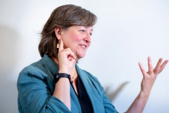 3/4 view portrait of Professor Michele Cooke gesturing to right of view, while gesturing with other hand towards her ear and hearing aid