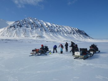 Team of scientists in winter clothing with snowbile in front of snow-covered arctic scene with mountain in background