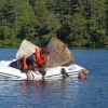 Dan Miller, Helen Habicht, and Benjamin Keilsing in an inflatable boat on a wooded lake, recovering sediment traps...