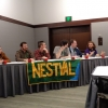 6 students seated, panel style, at table in hotel conference room, facing camera, with large banner displaying letters 'NESTVAL' draped over front of table.