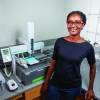PhD student Marsha allen smiling at camera, standing in front of analytical equipment