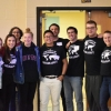 Members of U-Mass Geography club assembled for group photo in front of doorway in lecture all, smiling at camera and wearing Geography Club t-shirts